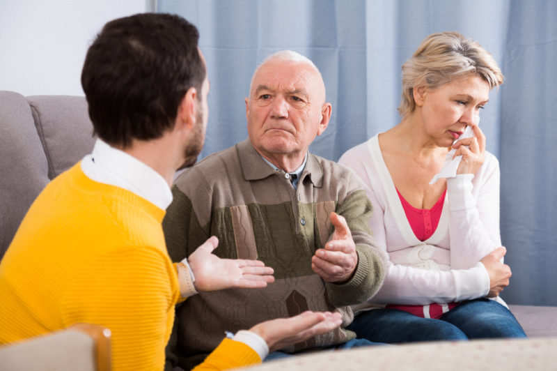 An adult man talks with his senior father and mother about aging. Talking to your parents about aging can be a difficult conversation, as pictured here.