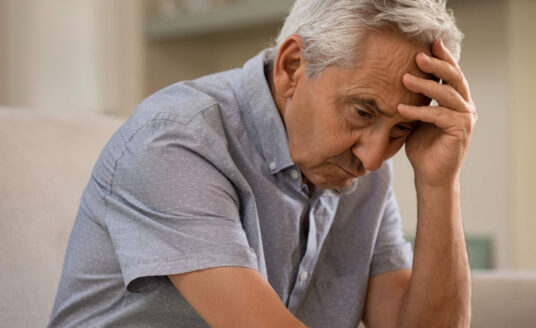 Elderly man looks stressed as he struggles with how to fight loneliness as a senior.