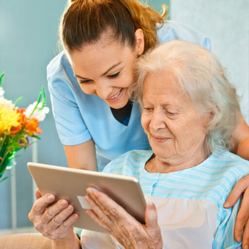 Respite care worker helps elderly woman use a tablet.