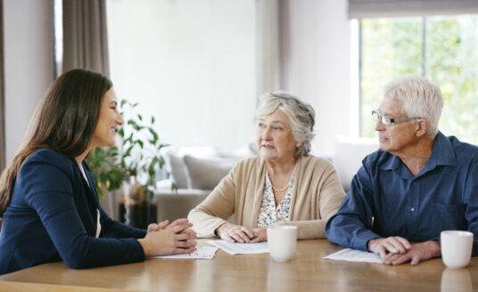 Advisor explaining health care documents to senior couple