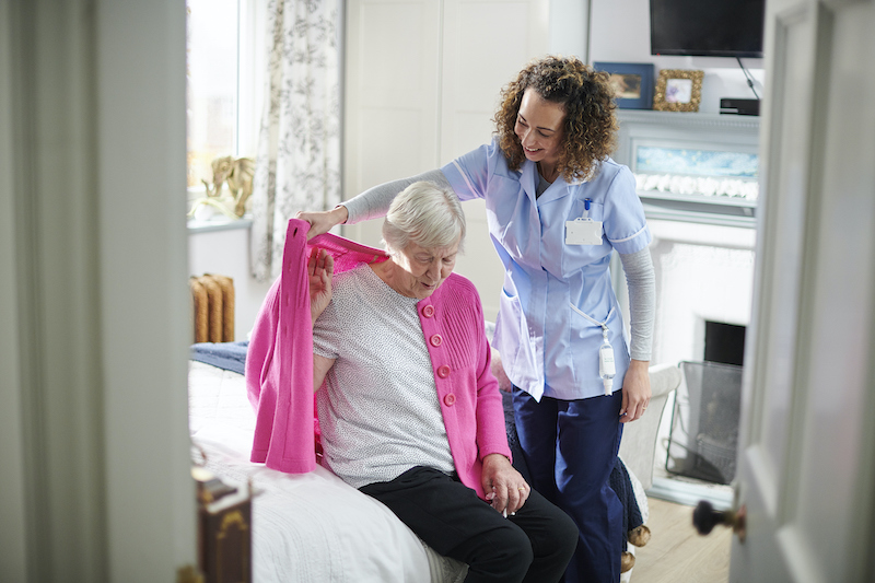 A professional caregiver helps a senior woman with Activities of Daily Living (ADLs).