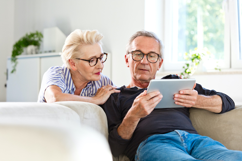 An older couple is touring senior living communities virtually from their home.