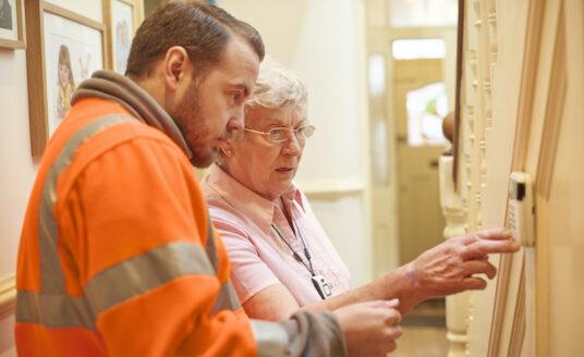Senior checks home thermostat for safety