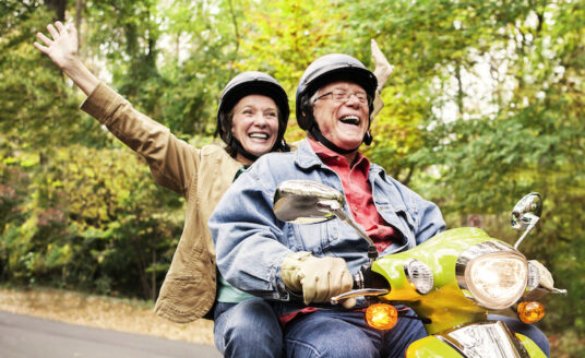 A happy senior couple riding a scooter as a way to stay active and healthy this fall