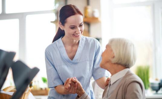 A nurse helps a senior woman at a memory care community