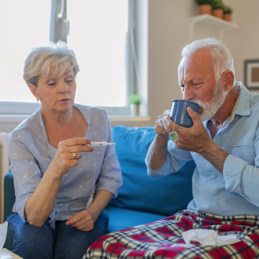 A senior woman takes her husband's temperature, watching for pneumonia symptoms.