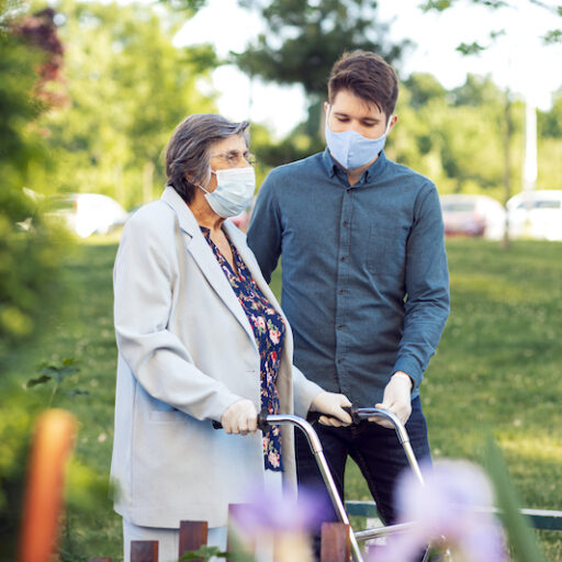 A senior woman walks with a staff member at her assisted living community.