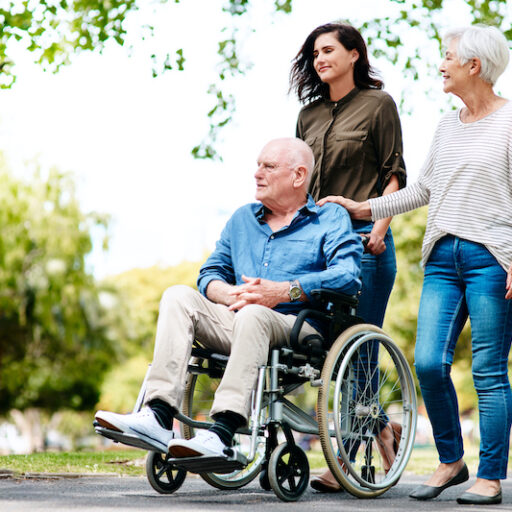 A senior couple, who needs different levels of care, takes a walk with their adult daughter.