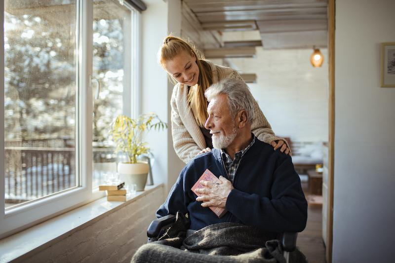 A senior man talks to a nurse at his skilled nursing home community.