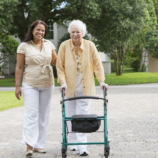 A woman walks with her senior mother, who recently moved home from Assisted Living