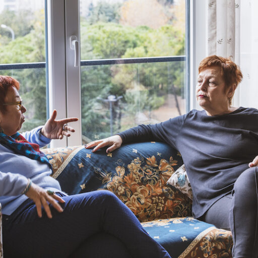 Adult child caring for an aging parent by sitting and having a discussion with her senior aged mother on a couch