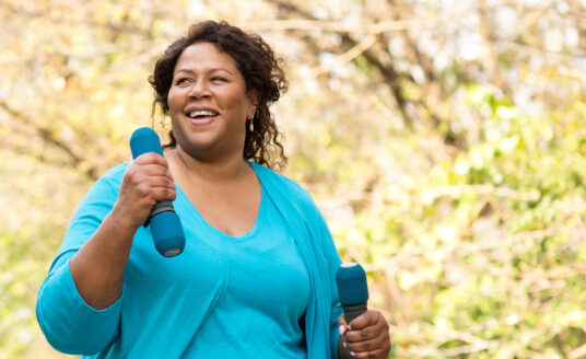 African American woman walking with weights and smiling.