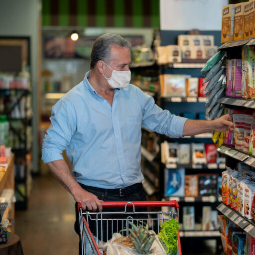 A man in the grocery store, following a heart-healthy shopping list.