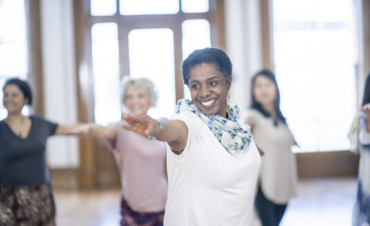 A woman of African American woman is indoors in a fitness studio. She is performing balance exercises and reaching her arms out.