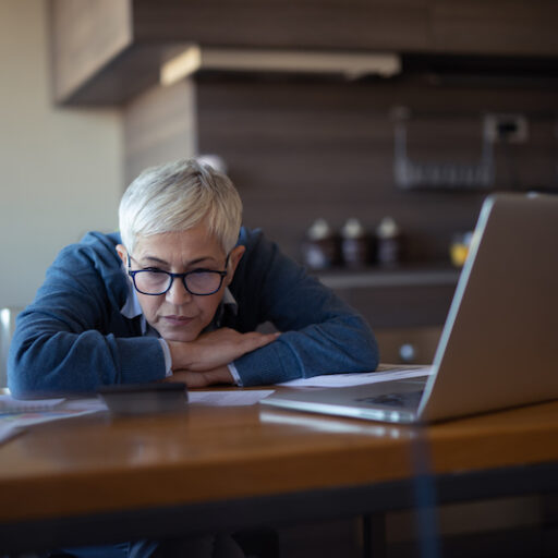 Older adult stressed out from multitasking while taking care of parent.