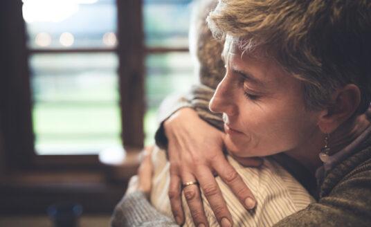 Adult child hugs elderly parent after receiving dementia diagnosis.