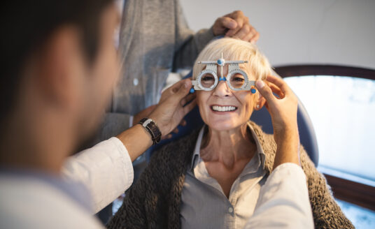 Senior woman having her eyesight checked by young optician at ophthalmologist's office in an effort to protect her vision.