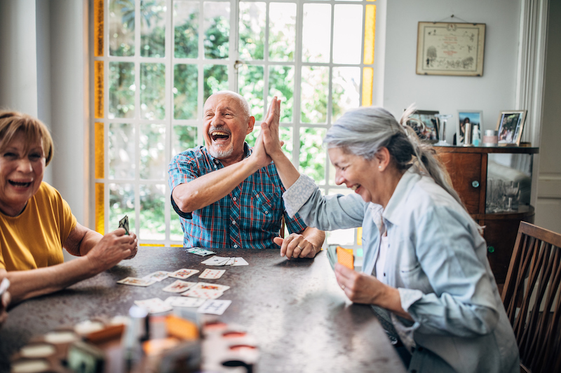 Group of older adults playing cards as a hobby..