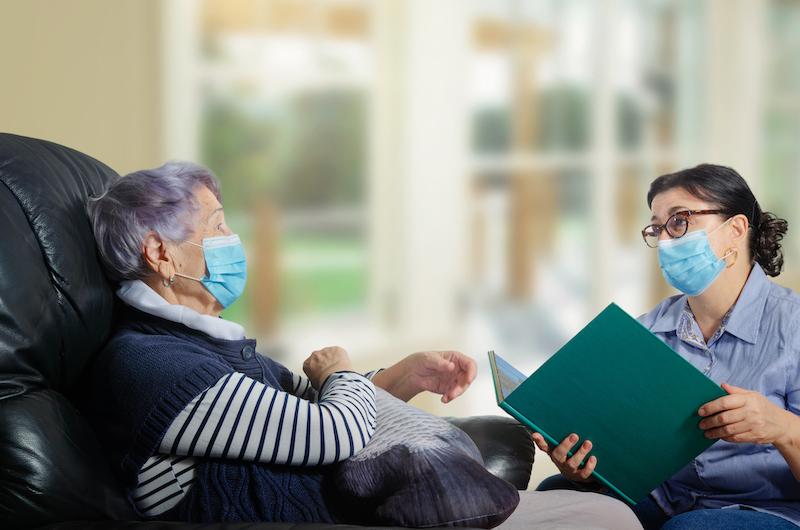 Caregiver assessing dementia patient for COVID-19.