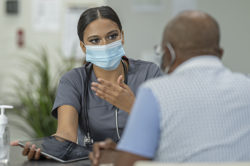 A senior patient and a female geriatric care manager meet in a medical clinic while wearing protective face masks to avoid the transfer of germs.