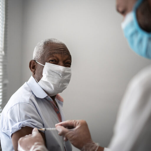 Nurse applying COVID-19 vaccine on elderly patient's arm wearing face mask