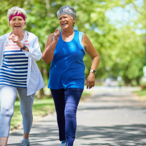 Two older women walking in a part to stay energized
