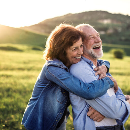 Side view of senior couple in golden years hugging outside in spring nature at sunset.