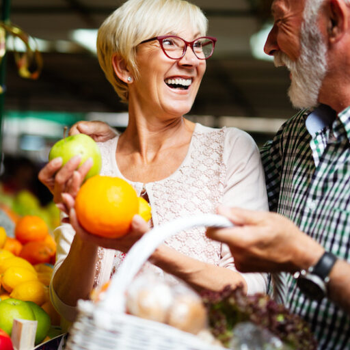 Senior couple shopping for spring vegetables and fruits at the market. Couple is shopping for spring nutrition for seniors.