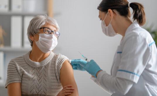 Doctor giving a senior woman a vaccination.