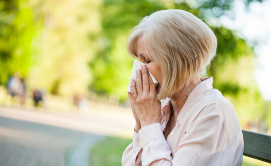 Adult woman is sitting in park and blowing nose. She is having an allergic reaction, a common spring health concern for seniors.