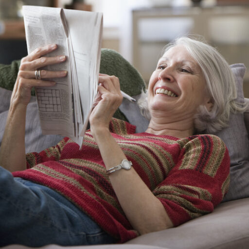 Senior woman staying sharp with mental exercises like Crossword Puzzles.