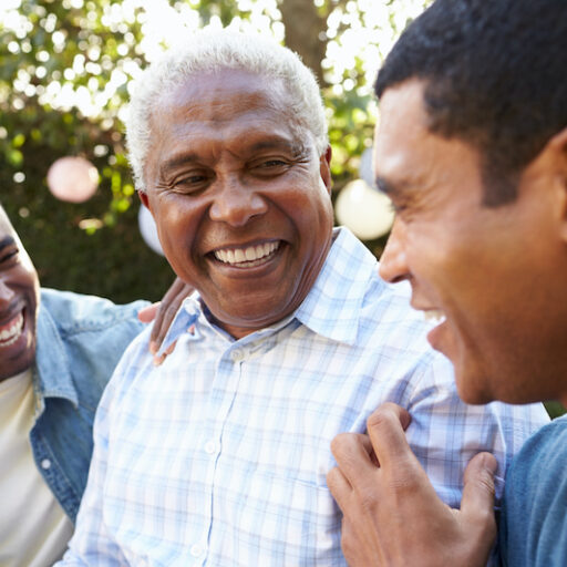 Senior man talking with his adult sons in garden, discussing Senior Stress Management