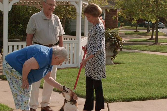 A senior man and woman stop to admire another senior woman's dog