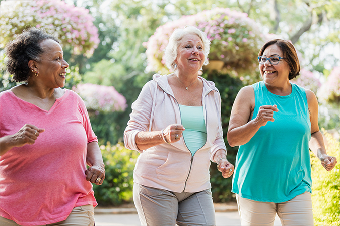 Three senior women speed walk together outside in the spring time
