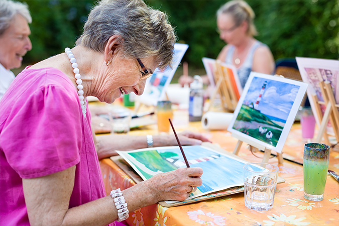 Senior women laugh and paint outdoors at The Oaks at Bethesda