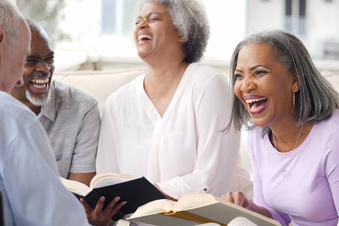 Four seniors - two men and two women - laugh over a book in book club