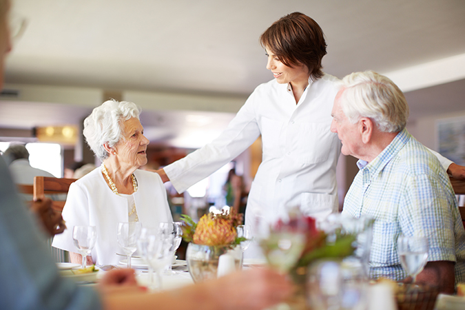 a senior man and woman are helped by a server at the dining hall of Barnes-Jewish Extended Care