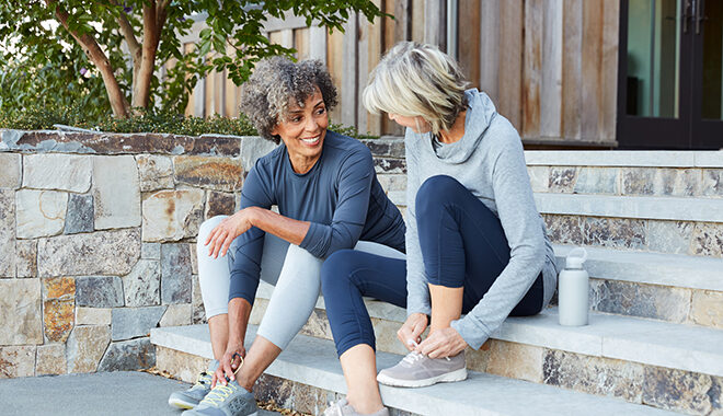 Two senior women sit on a stoop after a jog and discuss senior living options
