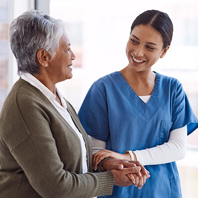 A nurse comforting a senior woman with a hand on her arm