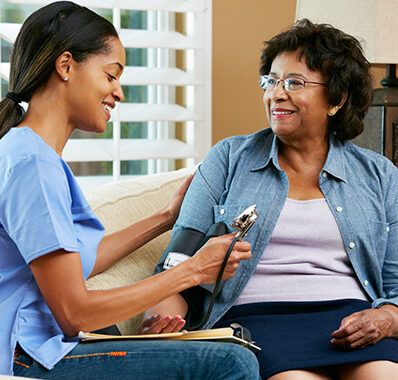 A young female nurse for Care in Your Home offers home care to a senior woman in her living room