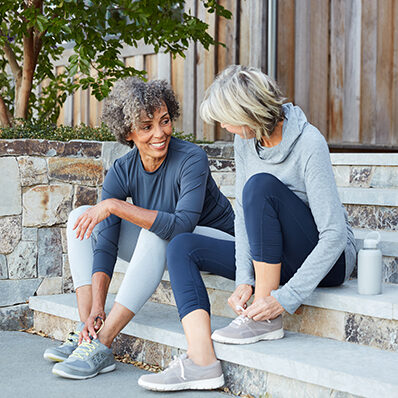 Two older women are seated on a stoop after a jog