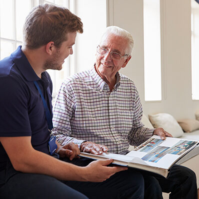 A younger man aids a senior man in memory support with a photo book