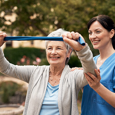 A young woman helps an older woman perform exercises with a resistance band