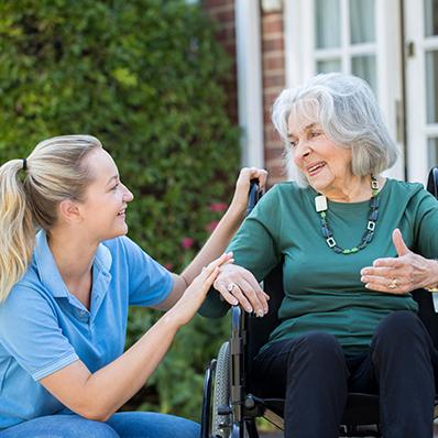 A senior woman in a wheelchair talking to a young female nurse