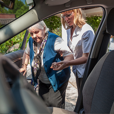 A senior woman getting assistance with getting in the car