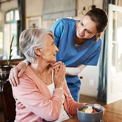 A young female nurse comforts a senior woman with a hand on her shoulder