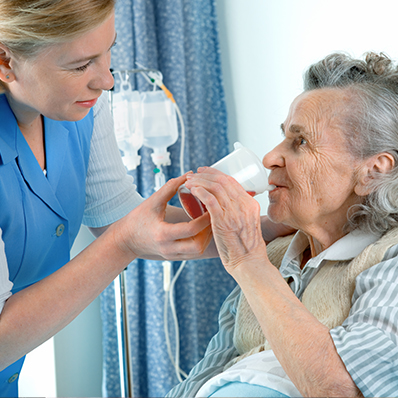 A senior woman receives hospice care as a young female nurse helps her drink fluids