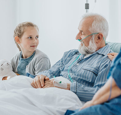 A senior man receiving hospice care talks to his granddaughter