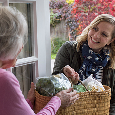 A senior woman receiving groceries delivered to her door by a young woman