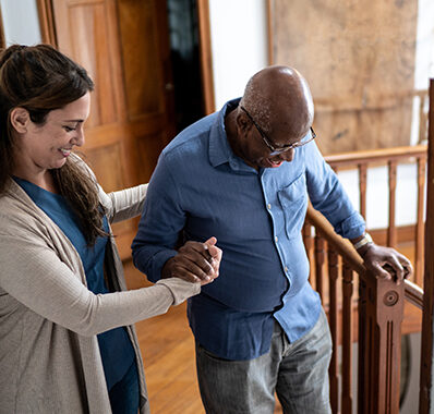 A young female nurse represents Care in Your Home by helping a senior man get down the stairs